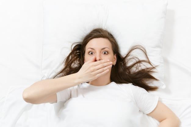 Vista superior da cabeça de uma jovem morena cansada, deitada na cama com lençol branco, travesseiro, cobertor. mulher chocada tapando a boca com a mão, passando um tempo na sala