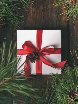 Vista superior da caixa branca do presente com a fita vermelha decorada, árvore dos cones do abeto e do pinho sobre a tabela de madeira.