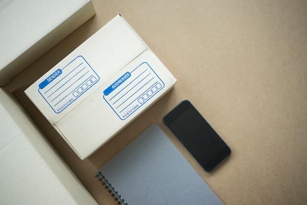 Vista superior da caixa de embalagem e smartphone com marketing on-line