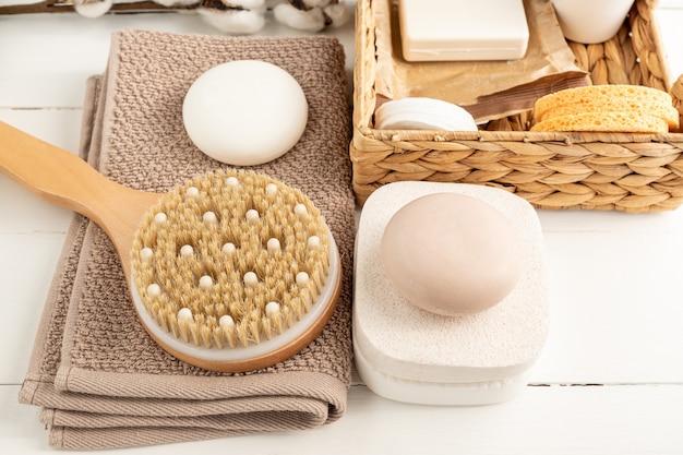 Vista superior da caixa de jacinto de água de acessórios de spa em casa com esponjas, sabonete e óleo natural, escova para massagem a seco e toalha de algodão em fundo de madeira.