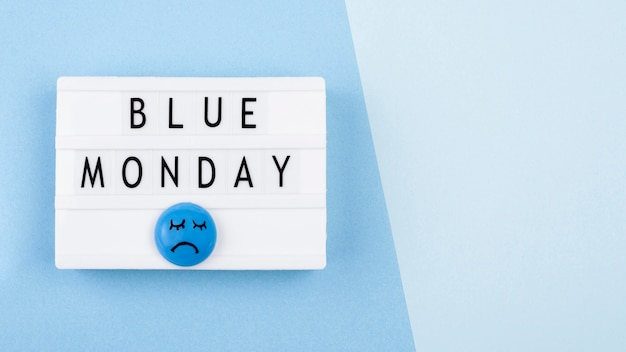 Vista superior da caixa de luz azul de segunda-feira com rosto triste e espaço de cópia