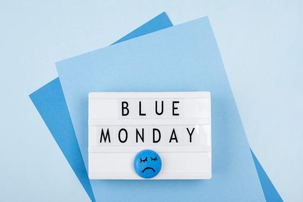 Vista superior da caixa de luz azul de segunda-feira com rosto triste e papel