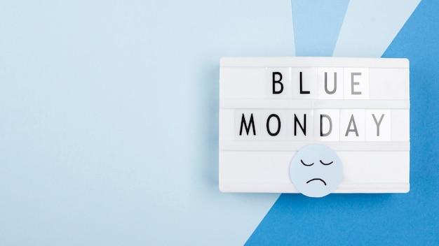Vista superior da caixa de luz com rosto triste para segunda-feira azul