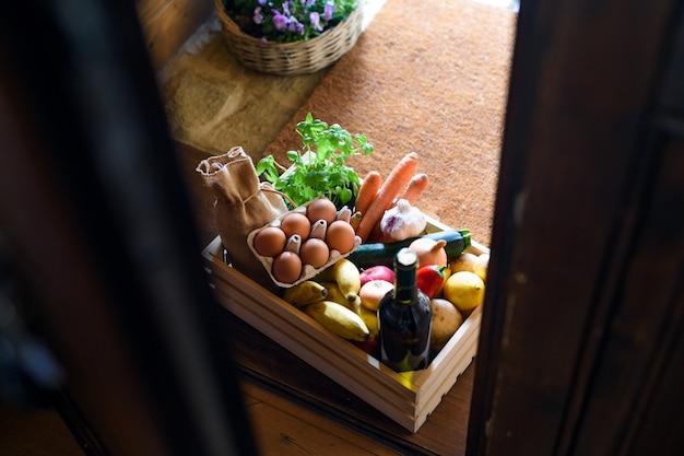 Vista superior da caixa de madeira com as compras de alimentos à porta, o vírus corona e o conceito de quarentena.