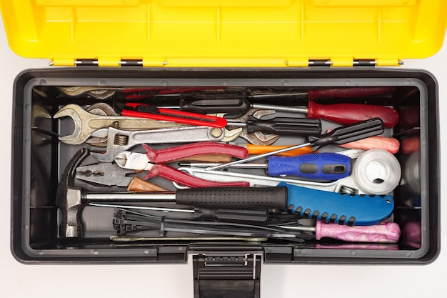Vista superior da caixa de plástico aberta com uma mistura de ferramentas e instrumentos isolados no branco