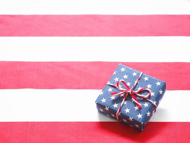 Vista superior da caixa de presente azul com padrão de estrela nas listras vermelhas e brancas de tecido de bandeira dos eua.