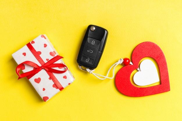 Vista superior da caixa de presente, chave do carro e coração de madeira