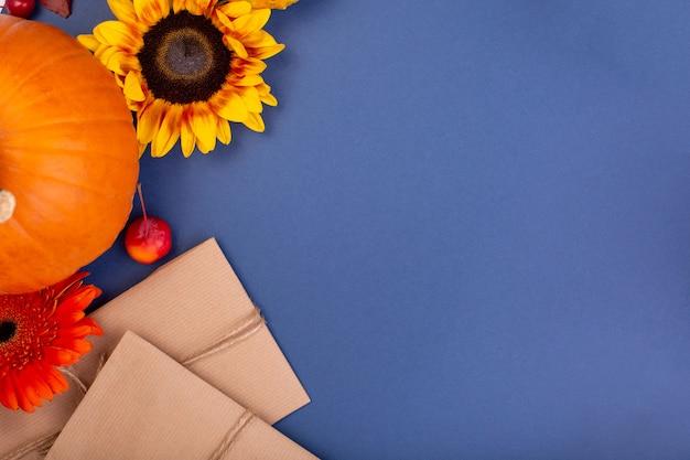 Vista superior da caixa de presente de artesanato com flores amarelas e laranja, carretel de corda e abóboras em fundo azul