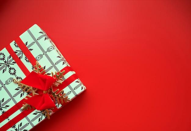 Vista superior da caixa de presente de natal com fita vermelha e arco e floco de neve dourada