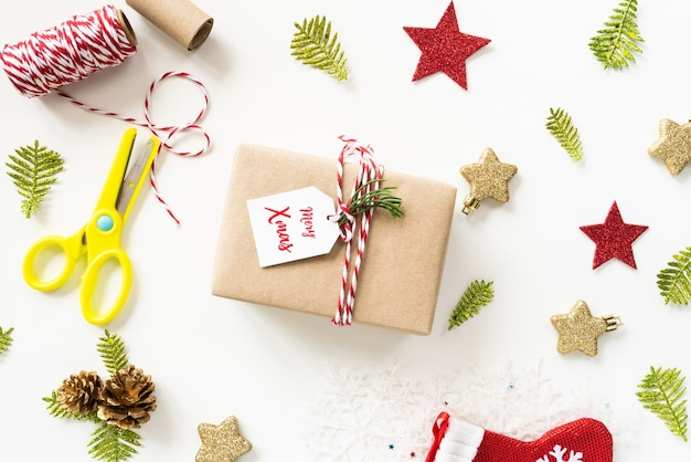 Vista superior da caixa de presente de natal com mensagem de marca, estrela vermelha e pinhas em branco backgrou