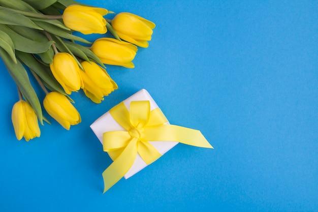 Vista superior da caixa de presente e tulipas amarelas no fundo azul
