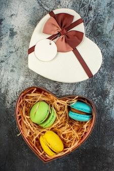 Vista superior da caixa de presente em forma de coração com deliciosos macarons em fundo escuro e gelado