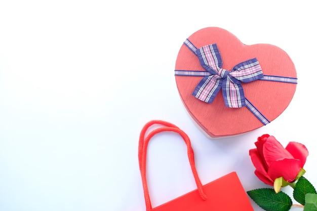 Vista superior da caixa de presente em forma de coração e flor rosa em branco