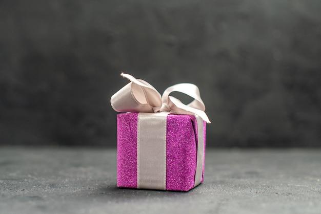 Vista superior da caixa de presente rosa com fita branca no espaço livre de superfície isolada escura