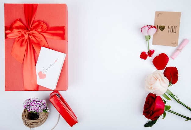 Vista superior da caixa de presente vermelha com um arco e rosas de cor vermelha e branca com grampeador e pequeno cartão postal em fundo branco com espaço de cópia