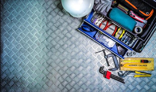 Vista superior da caixa e do capacete de ferramentas no fundo quadriculado da placa na oficina.