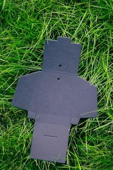 Vista superior da caixa preta vazia desdobrada para acessórios ou etiquetas de roupas na grama verde no verão com ...