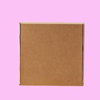 Vista superior da caixa quadrada fechada de papelão kraft em um fundo rosa