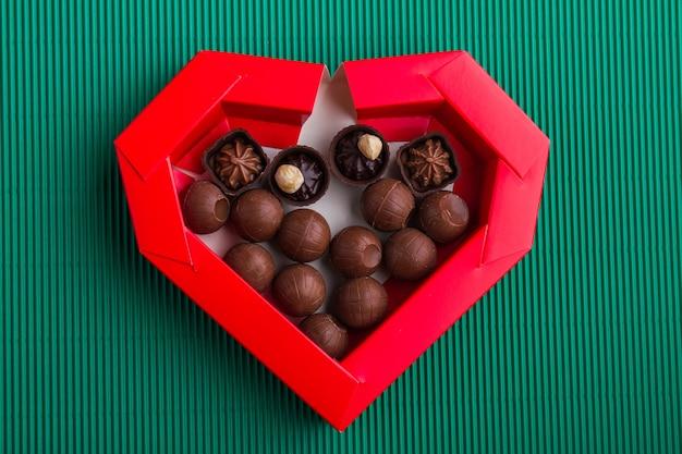 Vista superior da caixa vermelha em forma de coração com bombons de chocolate redondos. presente para o dia dos namorados.