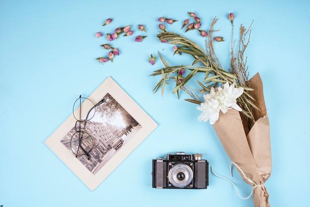 Vista superior da câmera antiga de foto com flor de crisântemo de cor branca em papel ofício e botões de rosa secos espalhados em azul