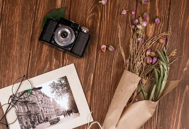 Vista superior da câmera antiga de foto e óculos com galhos secos de cor branca em papel ofício e botões de rosa secos espalhados na madeira