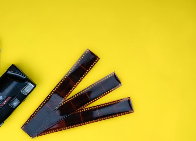 Vista superior da câmera antiga manual encontra-se e filme usado para despir-se em fundo amarelo