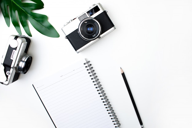 Vista superior da câmera de filme com caderno, lápis e folhas. isolado fundo branco.
