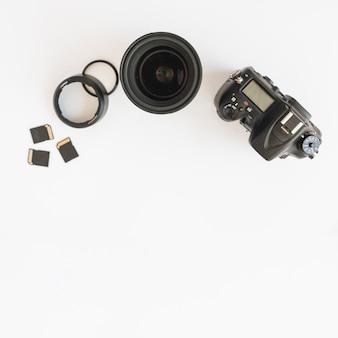 Vista superior da câmera dslr; cartões de memória e lente da câmera com anéis de extensão em pano de fundo branco