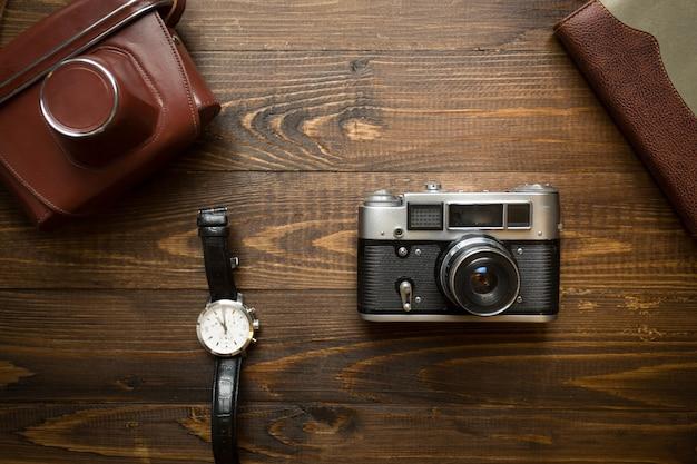 Vista superior da câmera manual vintage, caderno e relógios em fundo de madeira