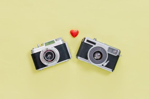 Vista superior da câmera velha vintage e pouco coração vermelho sobre fundo amarelo pastel.