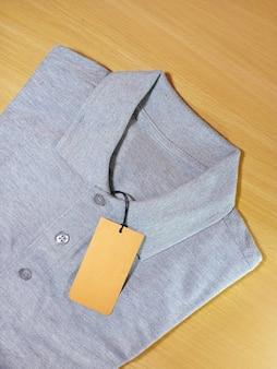 Vista superior da camisa pólo cinza com etiqueta de preço