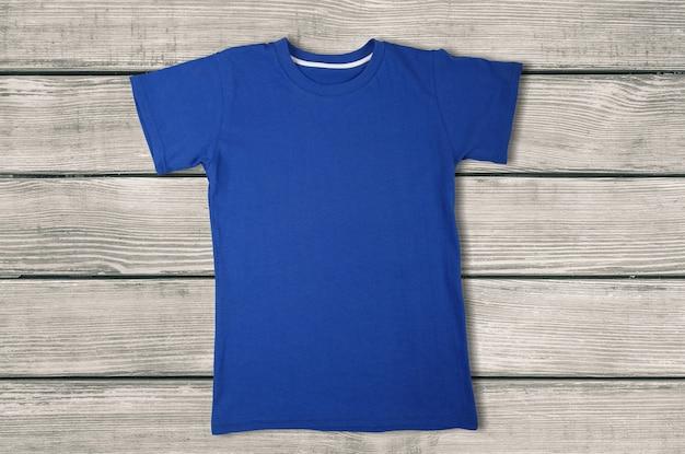 Vista superior da camiseta azul sobre fundo de madeira