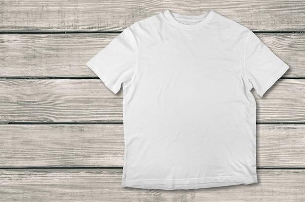Vista superior da camiseta branca com fundo de madeira
