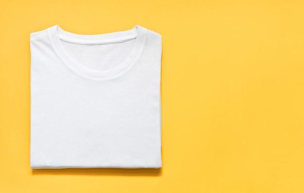 Vista superior da camiseta dobrada de cor branca sobre fundo amarelo