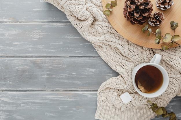 Vista superior da caneca de chá e pinhas com pulôver