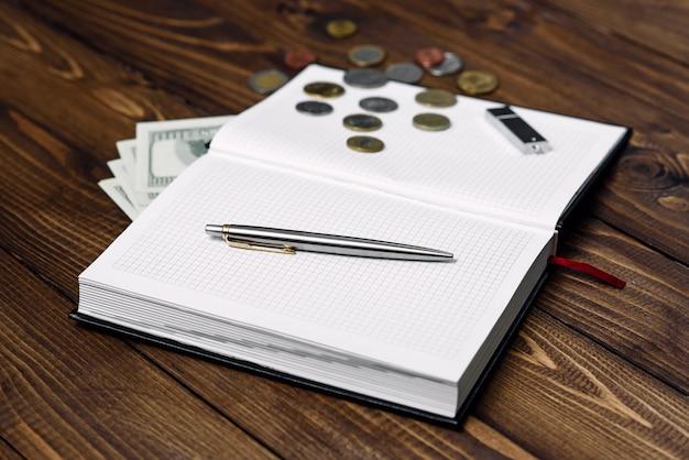 Vista superior da caneta, caderno aberto, pen drive, notas e moedas