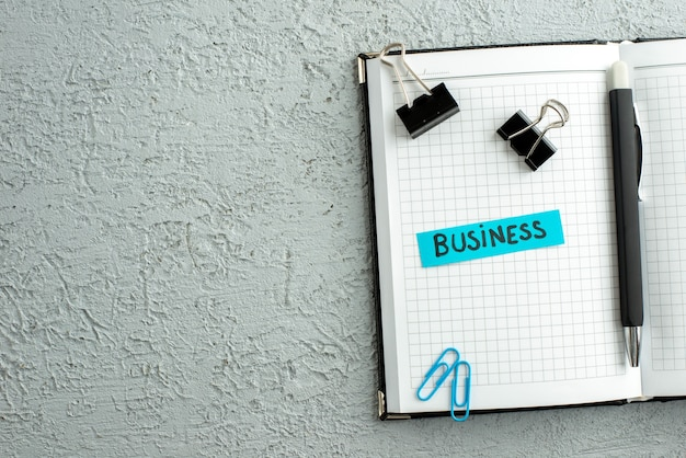 Vista superior da caneta de negócios de cor azul e caderno espiral aberto em fundo de areia cinza
