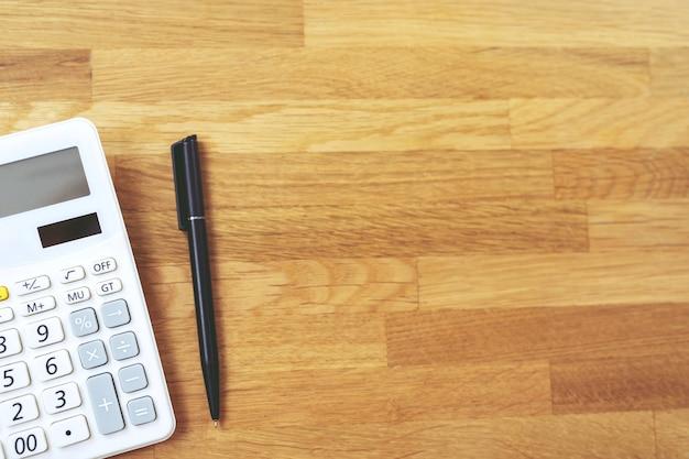 Vista superior da caneta preta com calculadora na mesa de trabalho vívida