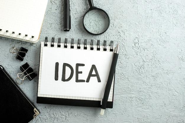 Vista superior da caneta sobre idéia escrevendo em folha branca na lupa de cadernos em fundo de areia cinza com espaço livre