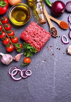 Vista superior da carne picada com especiarias e vegetais e mais comida na superfície preta
