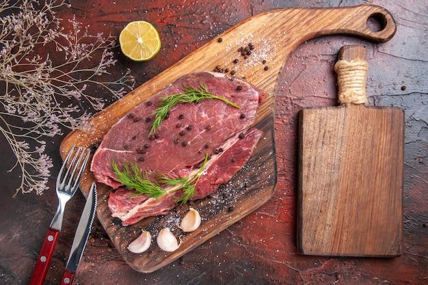 Vista superior da carne vermelha em uma tábua de madeira, alho, garfo e faca em fundo escuro