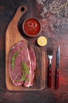 Vista superior da carne vermelha em uma tábua de madeira e ketchup em uma tigela pequena, garfo e faca em fundo escuro