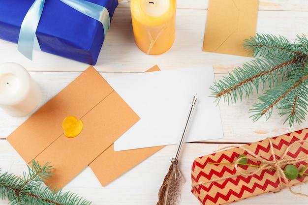 Vista superior da carta de natal, escrevendo em papel amarelo na madeira com decorações