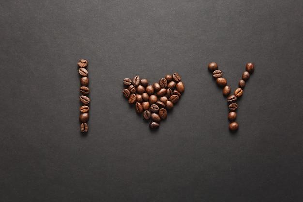 Vista superior da carta eu te amo - palavras de coração u feitas de grãos de café em fundo preto para o projeto. cartão de são valentim em 14 de fevereiro, conceito de férias. copie o espaço para anúncio.