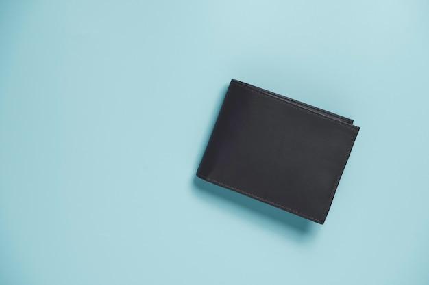 Vista superior da carteira de dinheiro de couro marrom com notas dentro sobre fundo azul e espaço de cópia.
