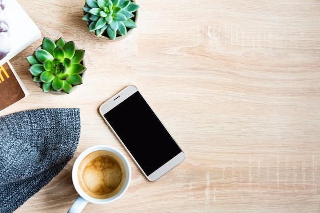 Vista superior da cena acolhedora em casa. livros, manta de lã, xícara de café, telefone e plantas suculentas sobre madeira. copie o espaço, mock-up.