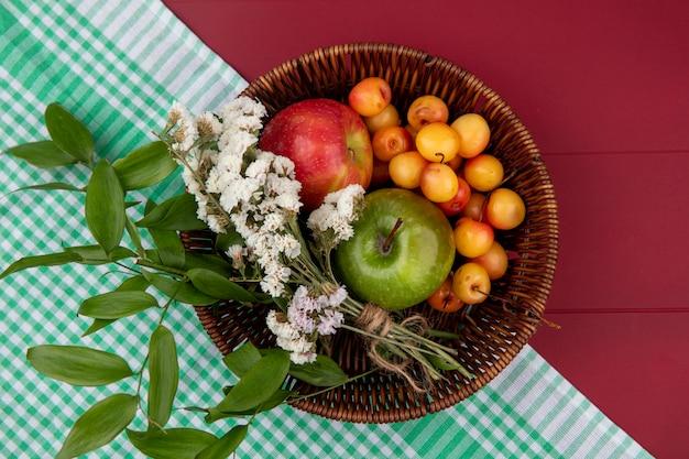 Vista superior da cereja branca com maçãs coloridas e flores em uma cesta sobre uma mesa vermelha