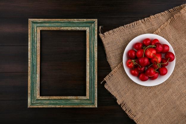 Vista superior da cereja em um prato em um guardanapo bege com uma moldura ouro-esverdeada em uma superfície de madeira
