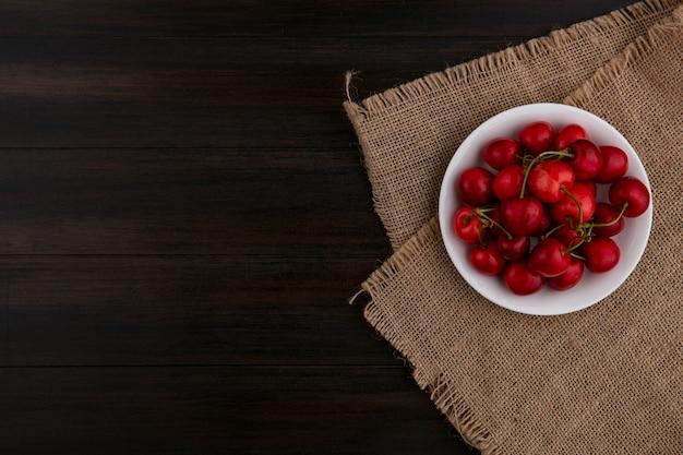 Vista superior da cereja em um prato em um guardanapo bege em uma superfície de madeira