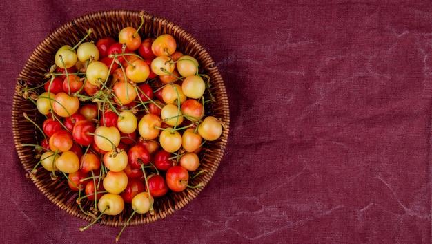 Vista superior da cesta cheia de cerejas amarelas e vermelhas no lado esquerdo e pano de bordo com espaço de cópia
